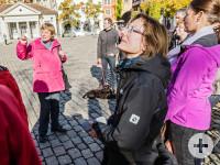 Eine Gruppe erhält gerade eine Stadtführung. Im Vordergrund ist eine Frau mit schwarzer Jacke im Seitenprofil dargestellt. Im Hintergrund ist eine Gästeführerin, die der Gruppe etwas erklärt. Sie stehen auf dem Schlossplatz.