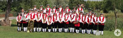 Es sind die Mitglieder der Knabenmusik Meersburg. Sie tragen die traditionelle Uniform in rot und weißt.