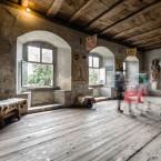 Blick in einen Innenraum der Burg Meersburg. Es sind drei Bilder im Hintergrund mit Rundbögen zu sehen.  Im Vordergrund laufen Besucher durch die Burg.
