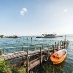 Blick vom Ufer aus auf einen den Bodensee. Im Vordergrund ist ein kleines orangenes Boot und ein Holzsteg zu sehen.