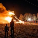 Blick auf ein Nachtbild. Im Hintergrund brennt ein großes Funkenfeuer, im Vordergrund sind die Umrisse zweier Personen zu sehen.