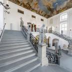 Blick in das Treppenhaus des Neuen Schloss Meersburg. Es sind Stuckverzierungen und eine Deckengemälde zu erkennen. An den Ecken der doppelten Treppe stehen Stauten römischer Götter. Alles ist in weiß gehalten.