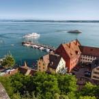 Blick von oben auf die Unterstadt und den Personenschiffhafen.  Es fahren gerade zwei weiße Personenschiffe aus der Hafenmole.