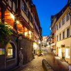 Blick entlang der Steigstraße in Meersburg. Es sind einige Fachwerkhäuser zu sehen.  Es ist Nacht und die Geschäfte und Lichter der Straße leuchten.