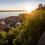 Blick von oben auf die Häuser der Unterstadt Meersburgs. Rechts ist die Burg Meersburg zu sehen.  Im Hintergrund geht gerade die Sonne unter und der Bodensee scheint in gelb und blau.