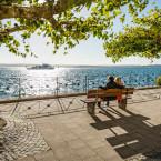 Zwei Menschen sitzen mit dem Rücken zum Betrachter auf einer Bank und blicken auf den Bodensee. Es fährt gerade ein Personenschiff vorbei.