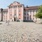 Blick über den Meersburger Schlossplatz auf das rosafarbene Neue Schloss Meersburg.  Es stehen einige grüne Bäume auf dem Schlossplatz.