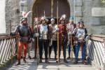 Männergruppe in Ritterrüstung stehen auf einer Brücke. In der Hand halten Sie historische Waffen