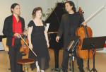 Eine Frau und zwei Männer stehen vor einem Klavier. Die beiden Männer halten ein Instrument in der Hand.