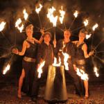 Zwei Frauen und zwei Männer stehen vor dunklem Hintergrund. Alle haben brennende Fackeln in der Hand.