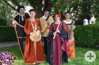 Musikergruppe steht in mittelalterlicher Kleidung vor einem Baum. In den Händen halten Sie unterschiedliche Musikinstrumente