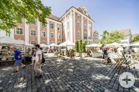 Auf einem Platz stehen weiße Zelte in denen Waren angeboten werden. Menschen laufen über den Platz. Im Hintergrund ist das barocke Gebäude des Neuen Schlosses zu sehen