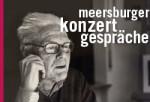 """Fotografie eines Mannes. Der Mann trägt eine Brille und hält seine rechte Hand an die Wange. Über dem Bild ist der Schriftzug """"Meersburger KonzertGespräche"""" abgebildet"""