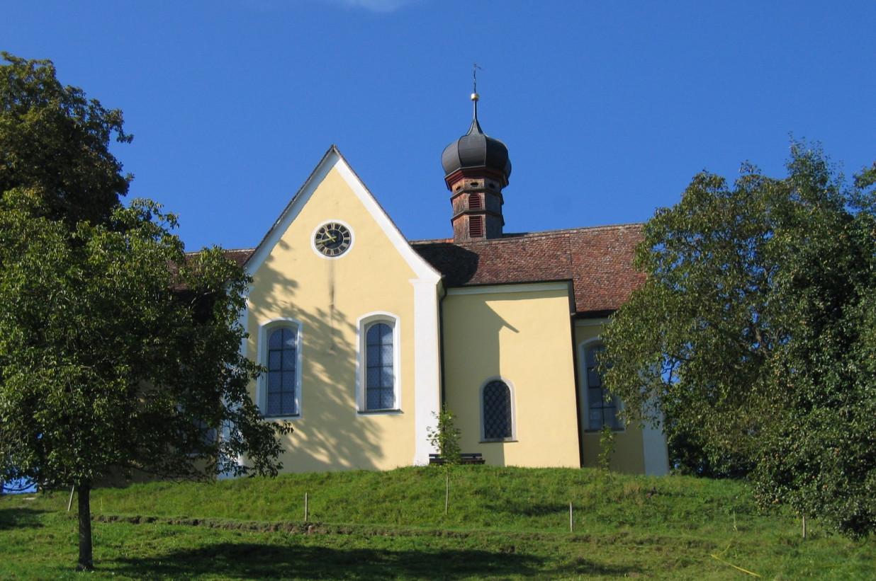 Blick über eine Wiese auf die Gelbe Baitenhausener Kapelle.