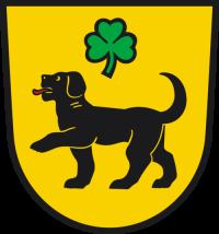Gelbes Wappen der Stadt Hohnstein mit einem schwarzen Hund. Über dem Hund schwebt ein dreiblättriges Kleeblatt in grün.