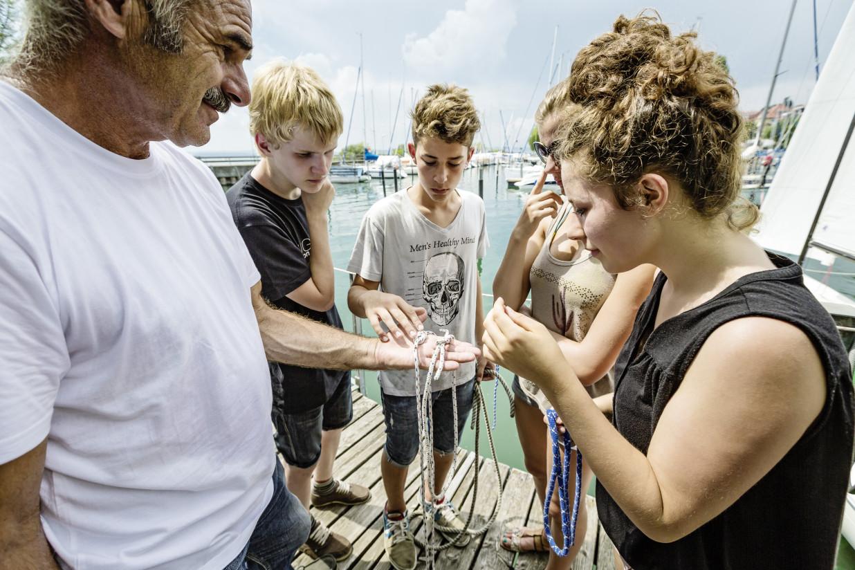 Mehrere Personen stehen im Halbkreis. Mittig ist die Hand eines Mannes zu sehen. Darauf liegen verschiedene Seile in verschiedenen Knoten.