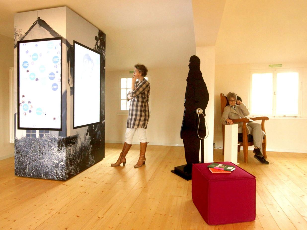 Auf der linken Seite steht eine Informationssäule. Auf der rechten Seite befinden sich mehrere Ausstellungsstücke.