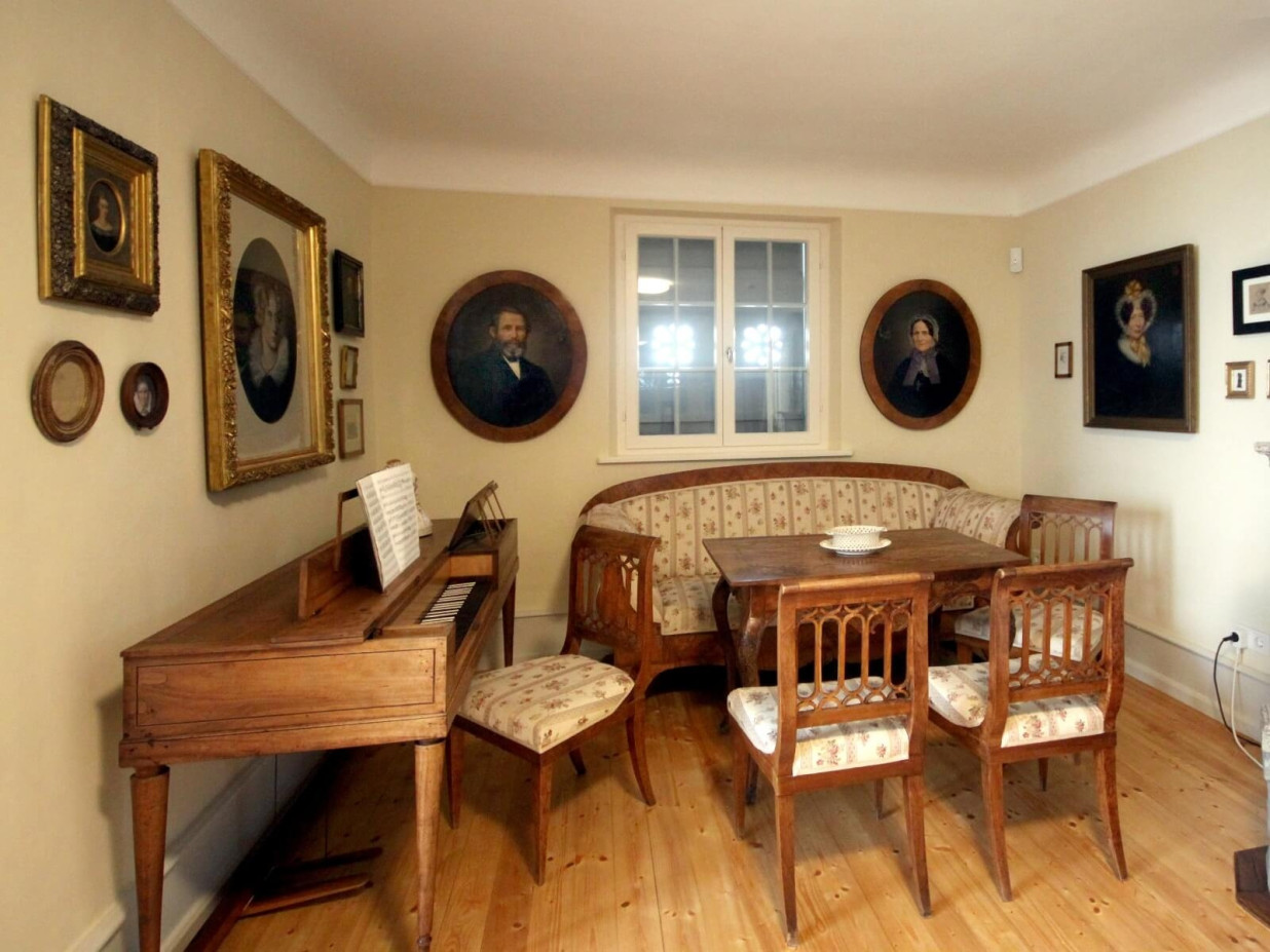 Blick in ein Arbeitszimmer des Fürstenhäusle. Es besteht aus einem hölzernen Schreibtisch sowie aus einer Sitzecke.