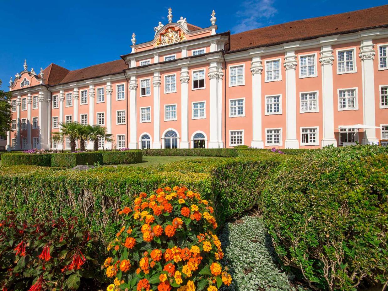 Blick frontal auf das Neue Schloss und seinen grünen Terrassenbereich. Das Schloss leuchtet in rosa, der Garten in grün und orange-rot.