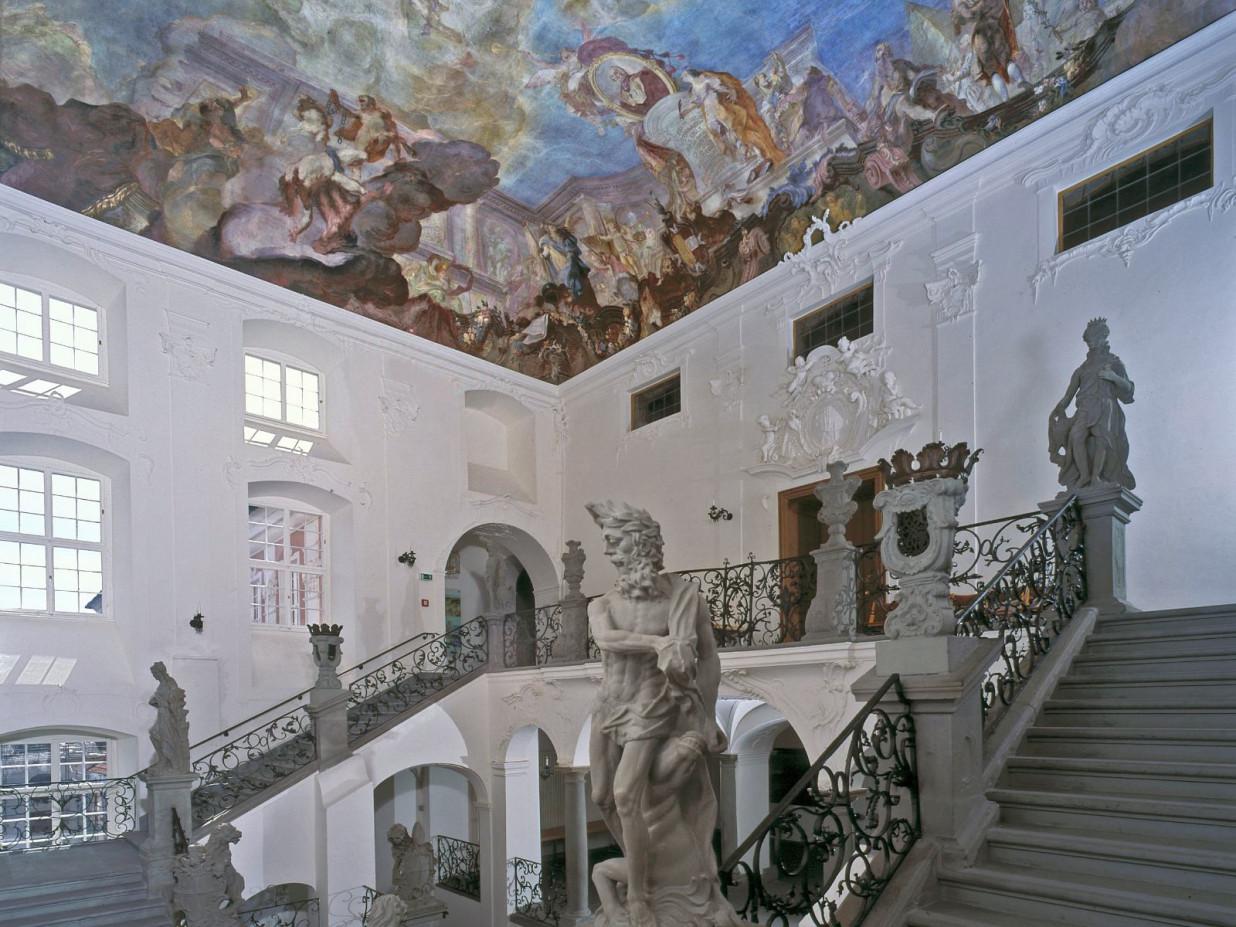 Dies ist eine Innenansicht des Neuen Schlosses. Das Foto zeigt ein steinernes, verziertes Treppenhaus und die bunt bemalte Decke.