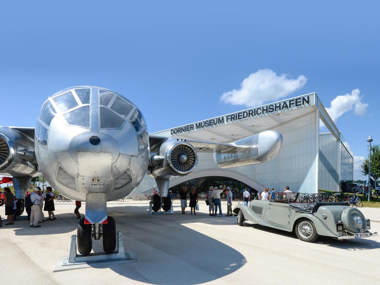 Blick auf die Front eines historischen, silbernen Flugzeugs. Rechts davon ein khakifarbenes Fahrzeug. Im Hintergrund das Gebäude des Dornier Museums Friedrichshafen.