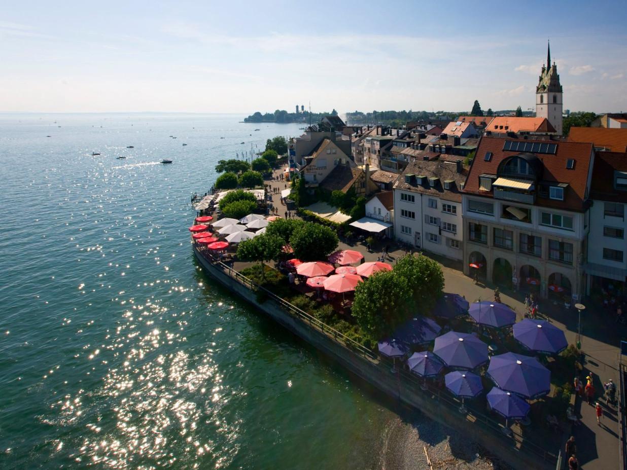 Fotografie der Stadt Friedrichshafen von oben. Links der Bodensee, rechts die Promenade und Teile der Stadt.