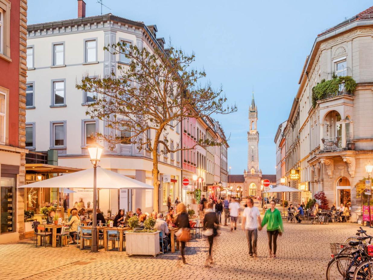 Blick in die Innenstadt der Stadt Konstanz. Es leuchten einige Straßenlaternen und Besucher tummeln sich in der Straße.