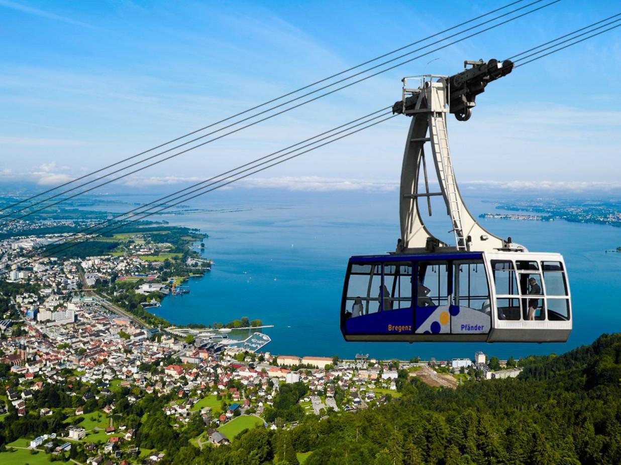 Abbildung der fahrenden Gondel der Pfänderbahn. Im Hintergrund ein Blick über Bregenz und den blauen Bodensee.