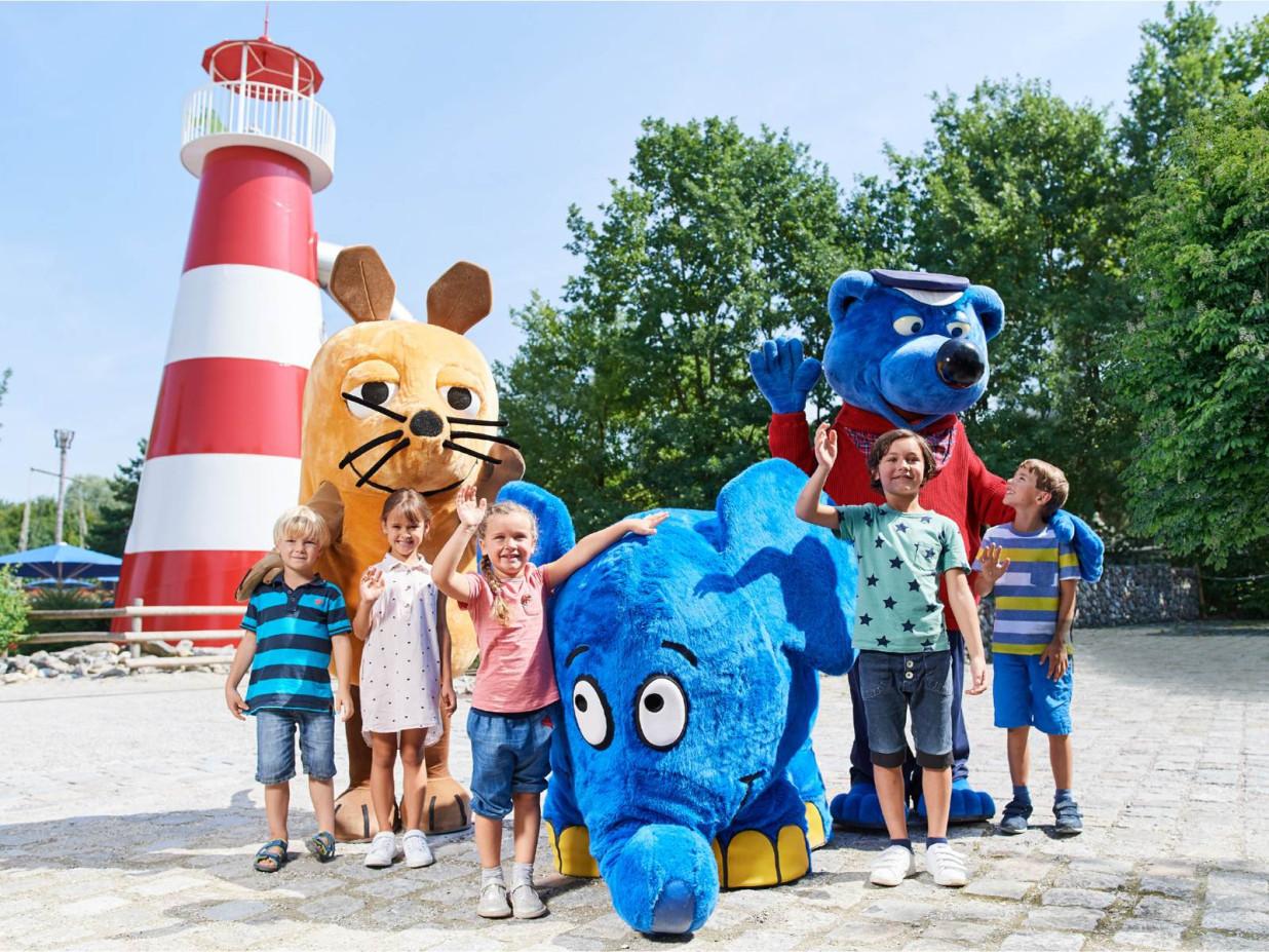 Gruppenbild vor dem Ravensburger Spieleland mit fünf Kindern und den Figuren Käpt'n Blaubär , der Maus und ihrem Begleiter dem Elefanten.