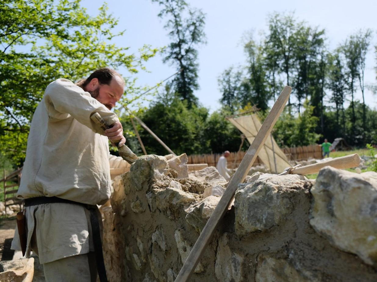 Fotografie eines Mannes, der in mittelalterlicher Kleidung eine Mauer baut. Die Mauer besteht aus ungleichen Steinen und Mörtel.