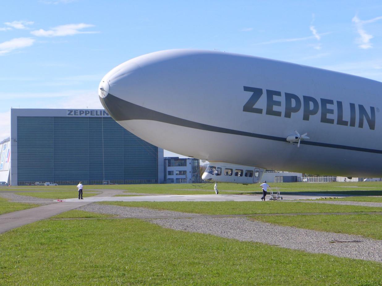 Von rechts ragt die Hälfte eines Zeppelin in die Fotografie. Im Hintergrund ist der Zeppelinhangar erkennbar.