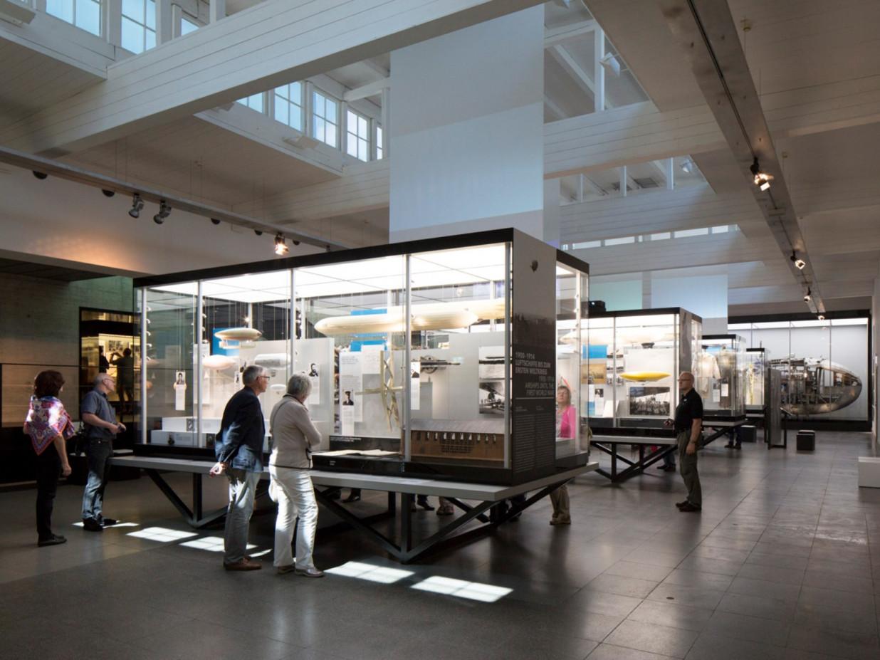 Blick in das Zeppelinmuseum Friedrichshafen. Es reihen sich einige Ausstellungsvitrinen aneinander und Besucher betrachten den Inhalt dieser.