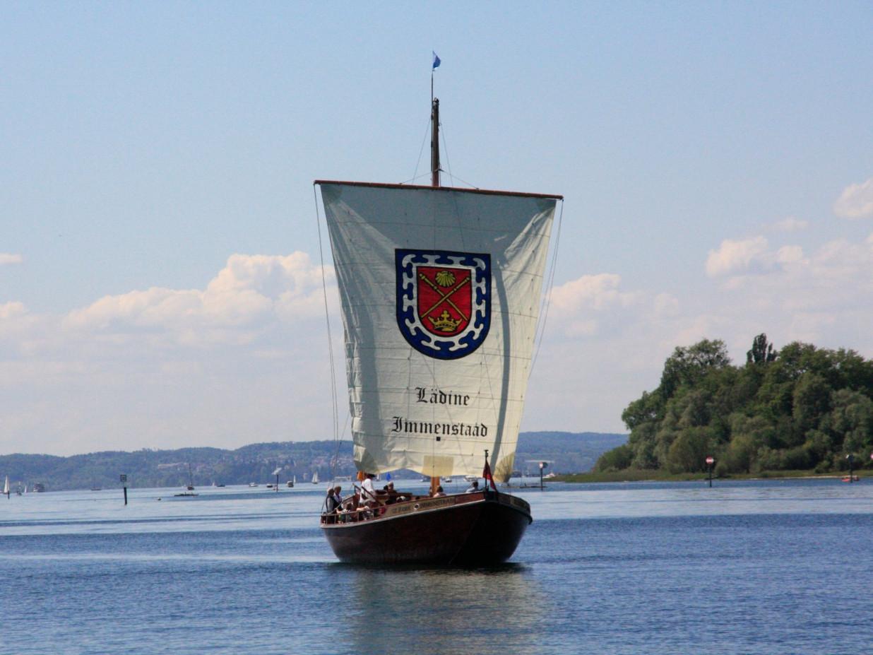 Blick über den Bodensee auf einen historischen Lastensegler, eine Lädine. Ein großes Wappen prankt auf dem weißen Segeltuch.