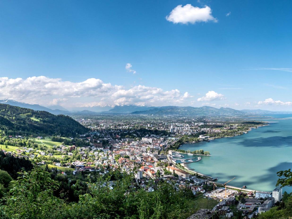 Blick von oben über die Stadt Bregenz. Rechts ragt ein Teil des Bodensees in das Bild. Links erstreckt sich die Stadt sowie Gebirge im Hintergrund.