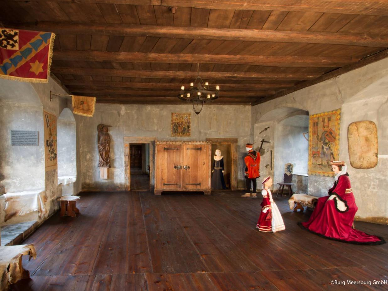 Das Foto zeigt einen Raum der Burg von innen. Dieser es gefüllt mit vier Staturen in mittelalterlicher Kleidung. Der Boden und die Decke sind aus Holz. Die Wände bestehen aus Stein.