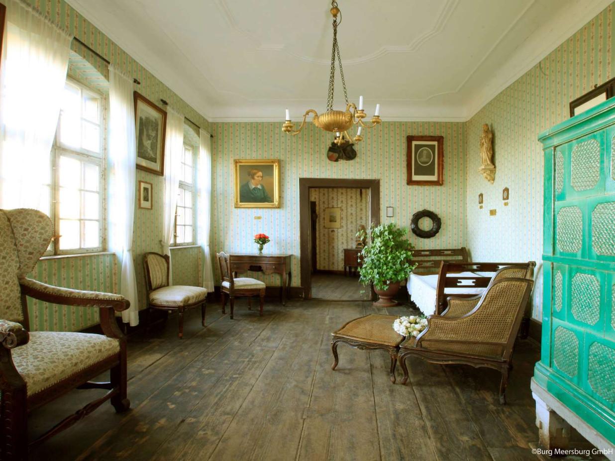 Dieses Bild zeigt das Sterbezimmer der Droste in der Burg. Es ist mit gemütlichen Möbeln und einem grünen Kachelofen eingerichtet.Sterbezimmer Droste