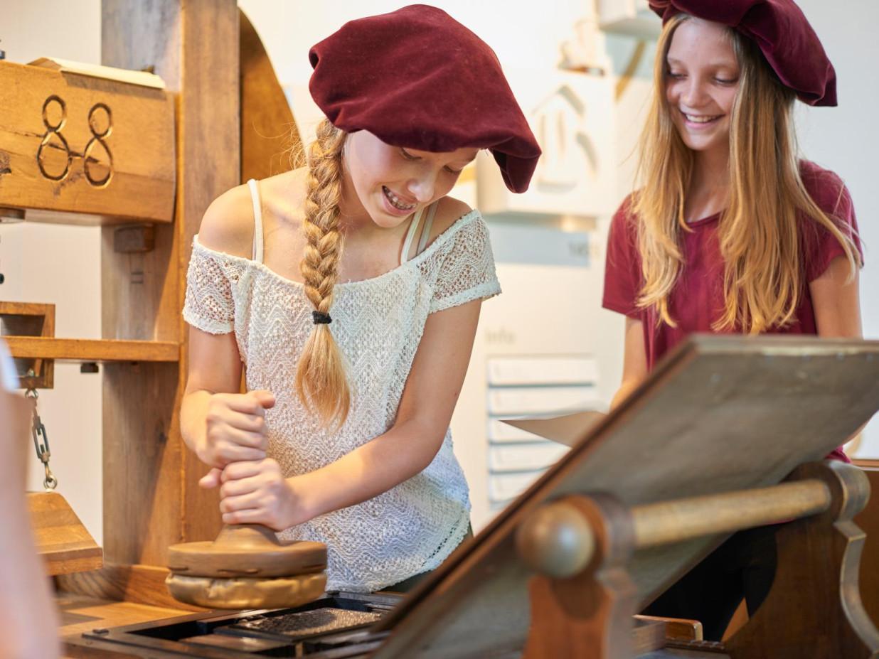 Zwei Mädchen mit roten alten Hüten probieren aus, wie früher der Buchdruck funktionierte. Dies geschieht an einer Holzmaschine.