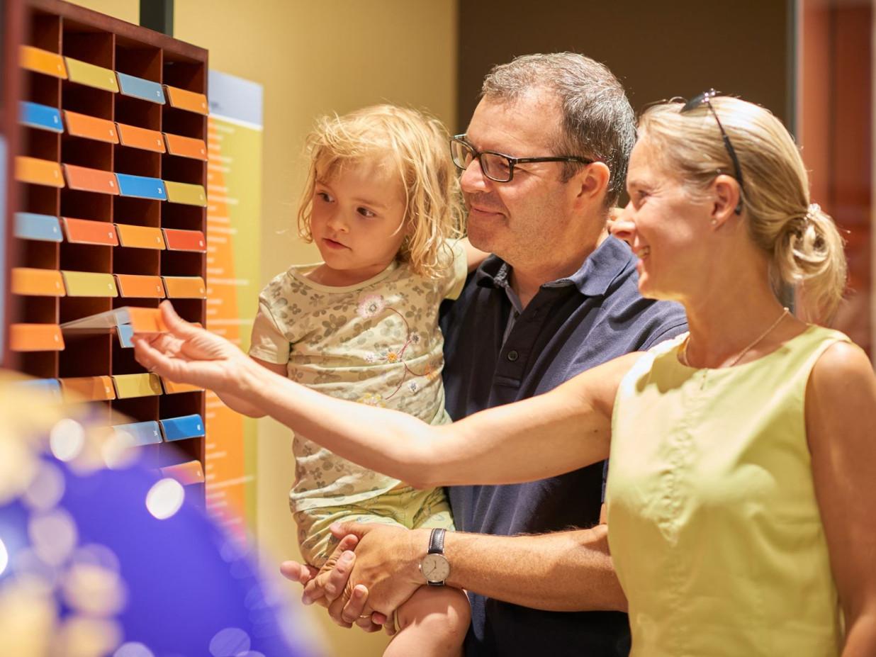 Eine Familie begutachtet eine Informationstafel der Bibelgalerie. Es ist eine Frau, ein Mann und ein kleines Kind auf dem Arm des Mannes zu sehen.