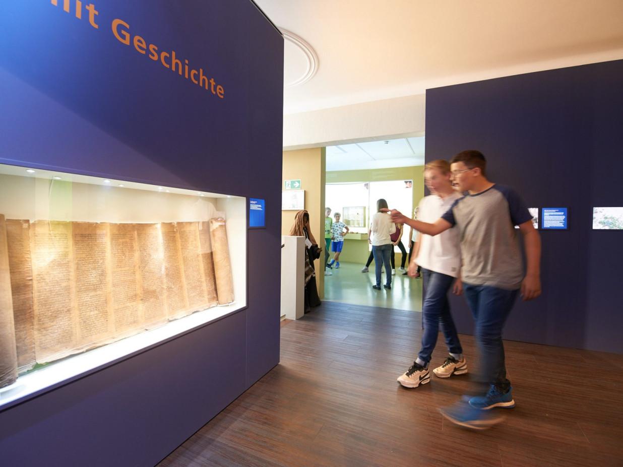 In einer großen Vitrine wird ein altes Schriftstück ausgestellt. Diese wird von zwei Jugendlichen begutachtet.