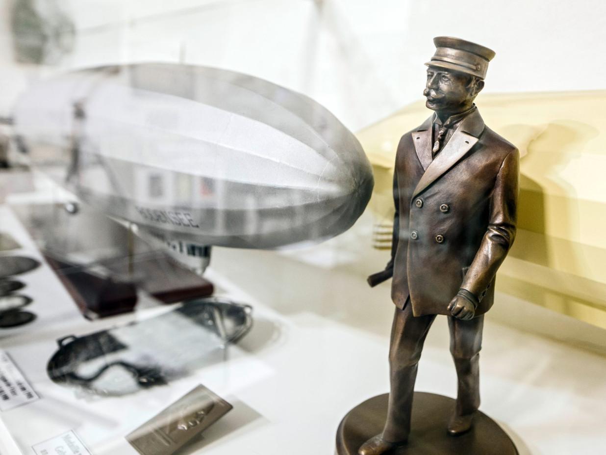 Es ist ein silbernes Modell eines Zeppelins, sowie eine metallische Figur eines Zeppelinpiloten zu erkennen.