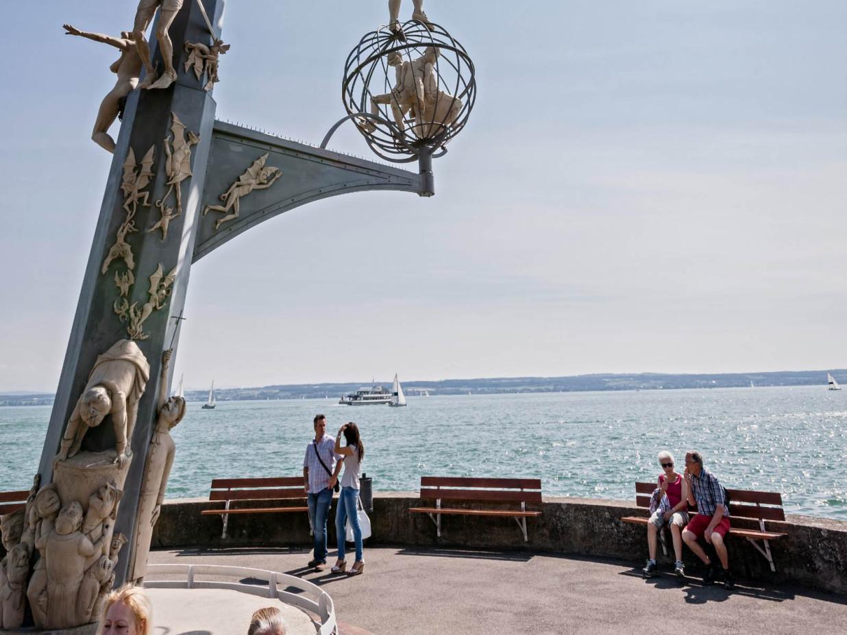 Foto des unteren Teils der Magischen Säule von Peter Lenk. Die Säule steht direkt am Bodensee und ist von Touristen umringt.