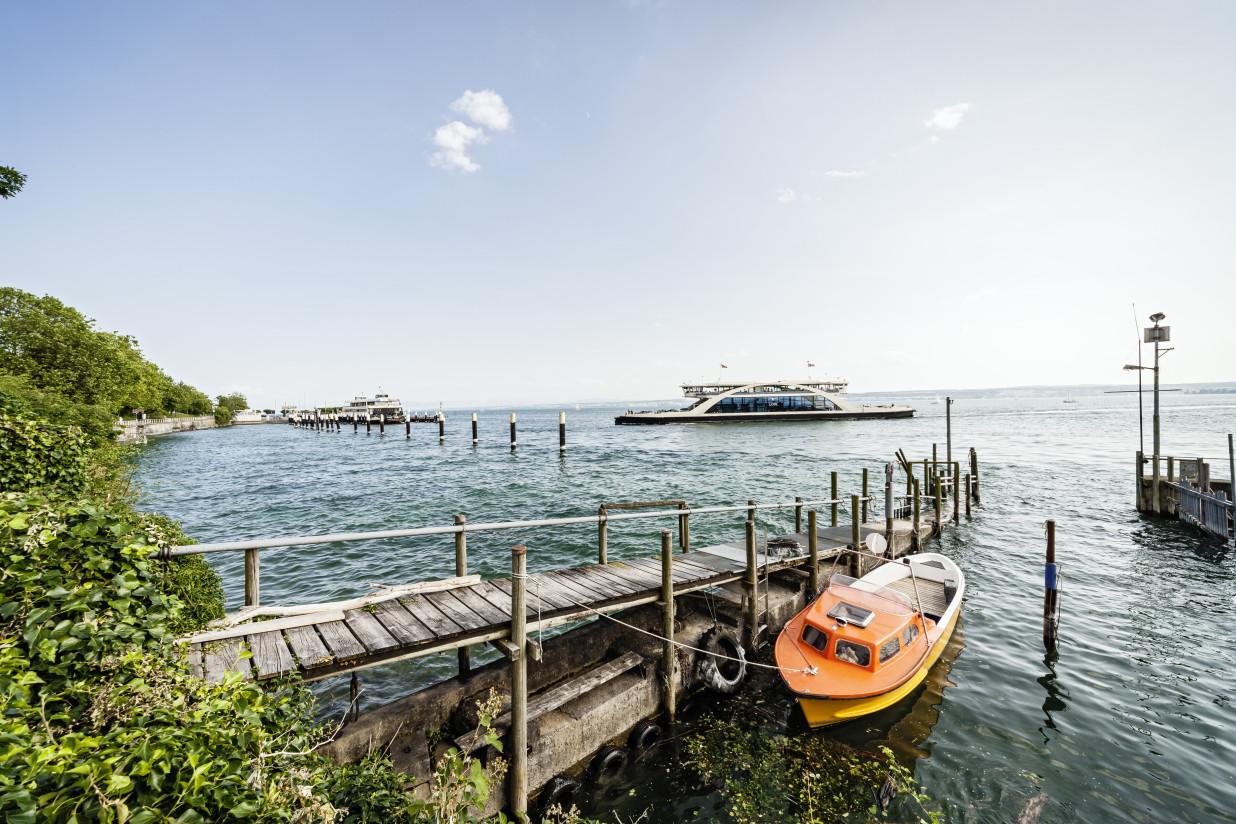 Im Vordergrund liegt ein orangenes,kleines Motorboot an einem hölzernen Steg. Im Hintergrund überquert die Autofähre gerade den Bodensee.