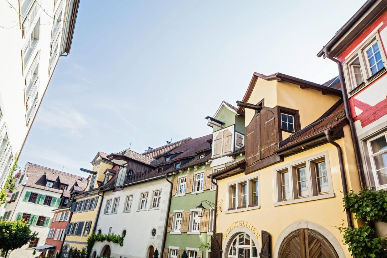 Blick entlang der Vorburggasse in Meersburg. Rechts reihen sich alte Häuser in den Farben gelb, grün, rot und weiß aneinander.