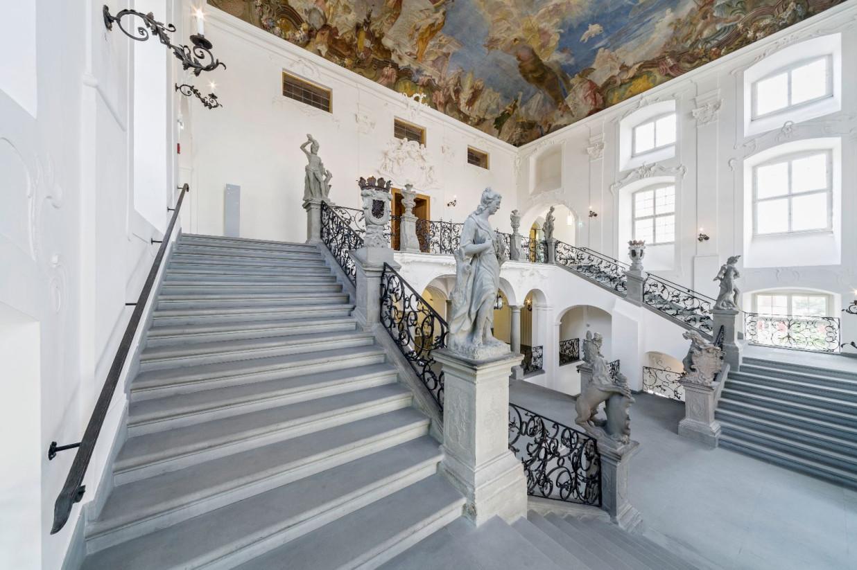 Es ist das Treppenhaus des Neuen Schloss abgebildet. Steinerne Treppen führen zuerst mittig nach oben. Sie teilen sich in eine linke und eine rechte Treppe.  An der Decke ist ein aufwendiges und buntes Gemälde.