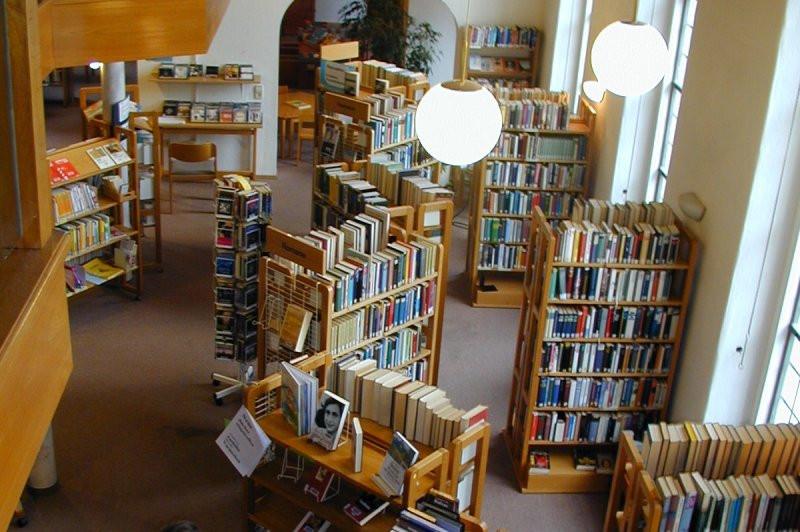 Das Foto zeigt einen Teil der Stadtbücherei von oben. Mittig reihen sich hellbraune Bücherregale in S-Form auf. Recht im Raum stehen vereinzelt die gleichen Regale. Zwei Lampen in Kugelform in das Bild.