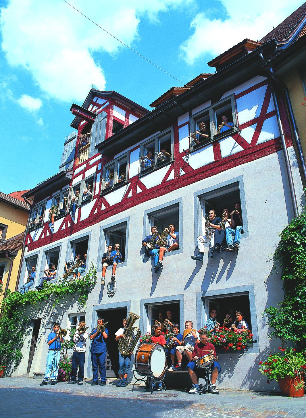Blick von außen auf das Haus der Jugendmusikschule. Es sitzen die verschiedenen Schüler aus den Fenstern und stehen vor dem Gebäude.