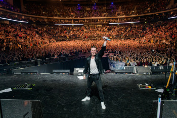 Ben Zucker inmitten eines Konzertes mit Publikum im Hintergrund.