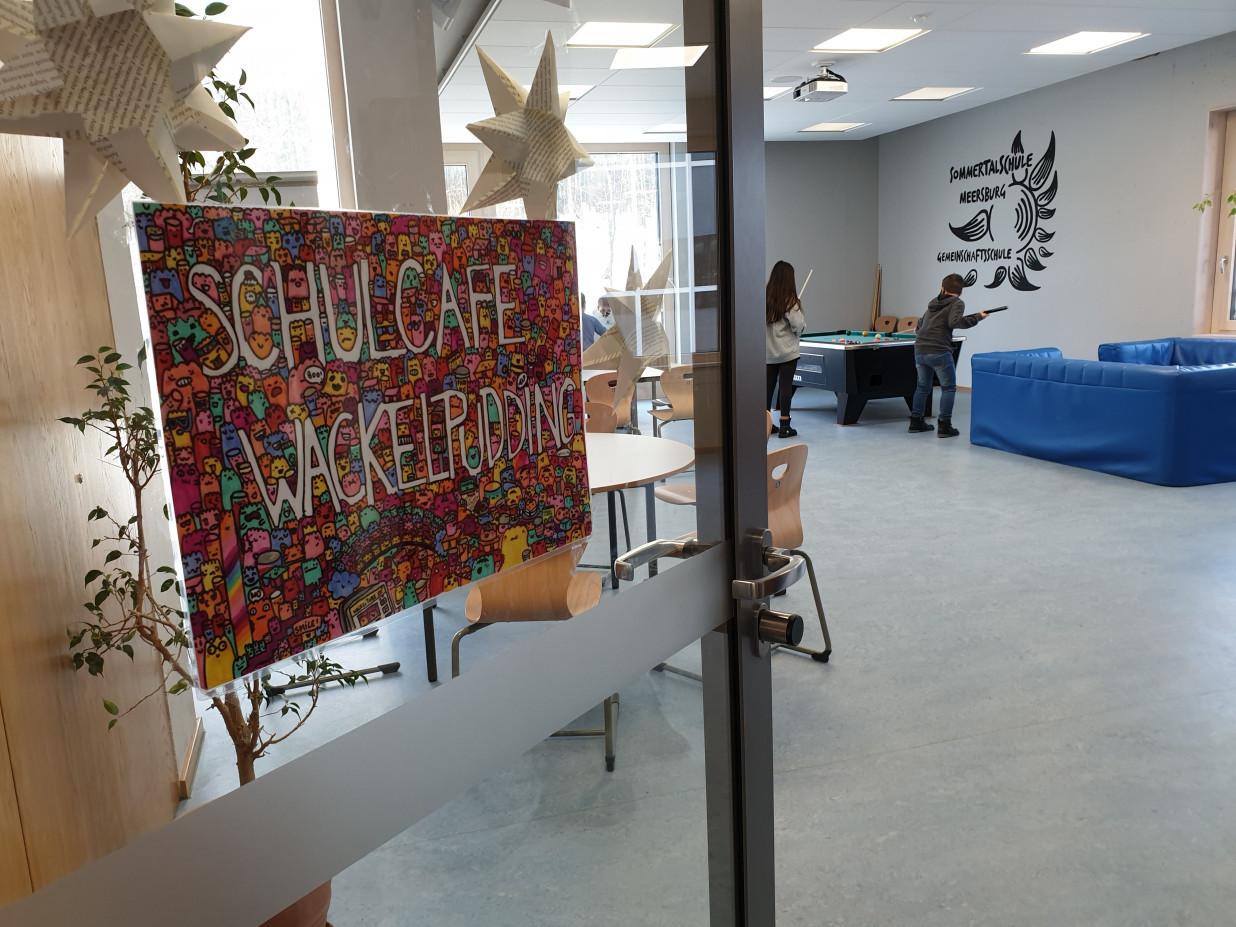 Blick entlang der geöffneten Türe des Schulcafé Wackelpudding. Im Hintergrund steht ein Billardtisch sowie einige Sitzmöbel.