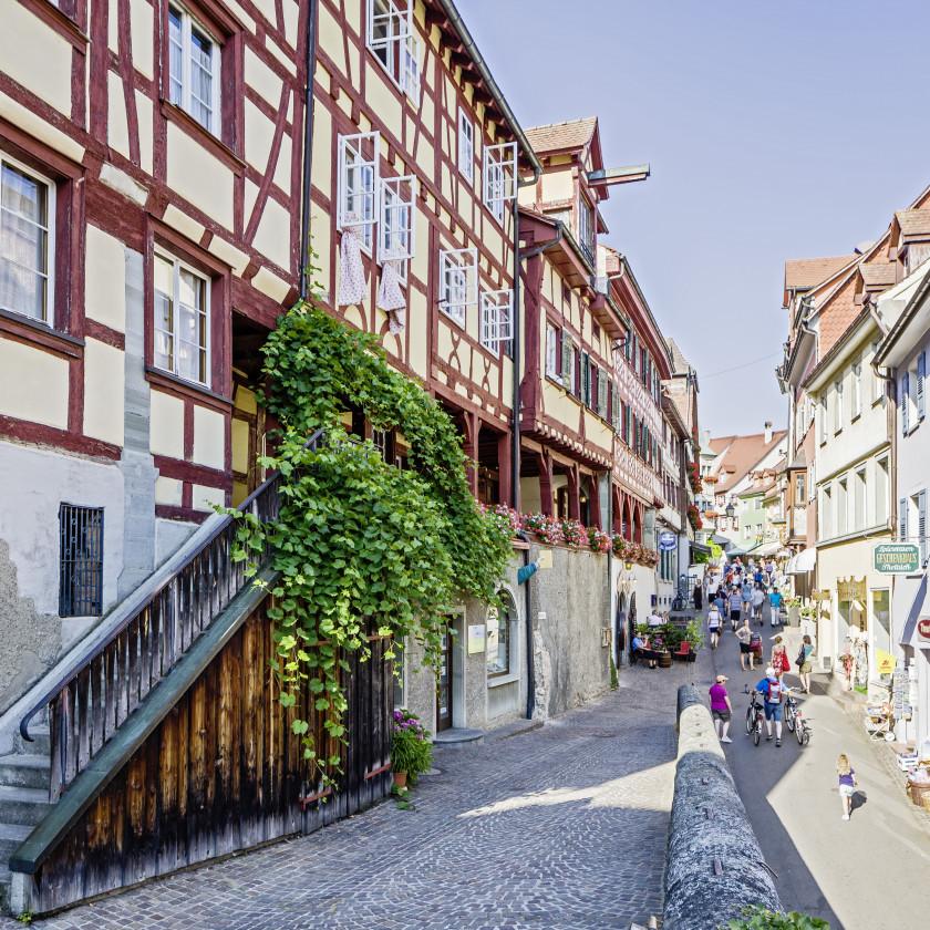 Blick entlang der Steigstraße Meersburgs. Links sind einige Fachwerkhäuser zu sehen. Es sind einige Menschen in der Straße unterwegs.