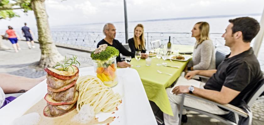 Im Vordergrund ist ein Teller mit einem Hauptgericht zu erkennen. Im Hintergrund sitzen vier Personen an einem Restauranttisch, der direkt an der Promenade Meersburgs steht.